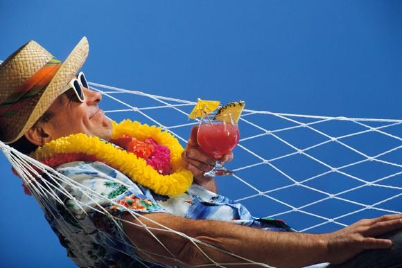 a man in a flowered shirt a hat and sunglasses and hawaiian lei around his neck lies in a hammock and holds a fruity drink.