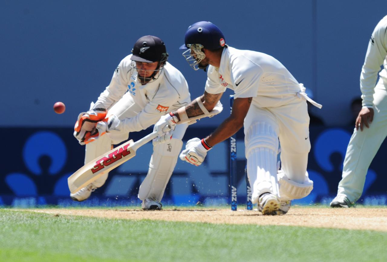 India's Shikar Dhawan, right, sweeps past New Zealand's wicket keeper BJ Watling on the fourth day of the first cricket test at Eden Park in Auckland, New Zealand, Sunday, Feb. 9, 2014. (AP Photo/SNPA, Ross Setford) NEW ZEALAND OUT