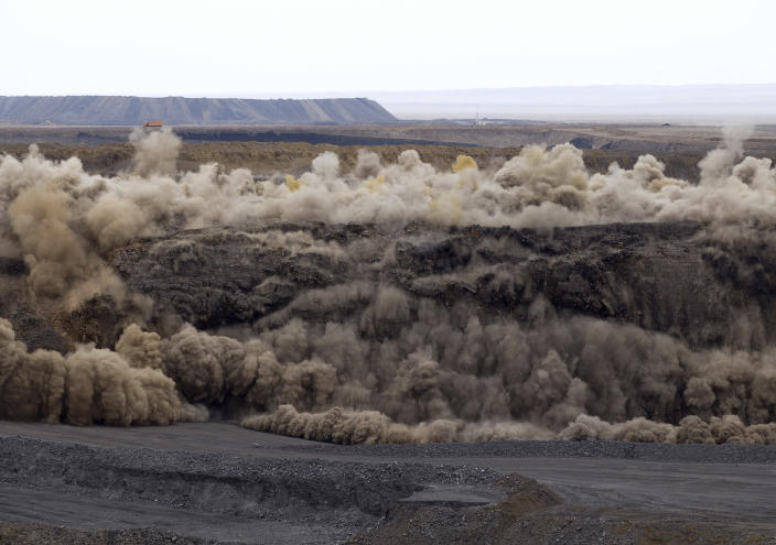 In this photo taken on July 6, 2012, miners use explosives to blast a section of the Erdenes Tavan Tolgoi coal mine in Tavan Tolgoi, southern Mongolia. Fully 90 percent of Mongolia's exports - coal, copper, cashmere and livestock - go to China, which in turn sends machinery, appliances and other consumer goods that account for a third of Mongolian imports. The rising trade with China now amounts to three-fourths of Mongolia's economy, one of the highest ratios in the world, according to an Associated Press analysis of IMF trade data. (AP Photo/Andy Wong)