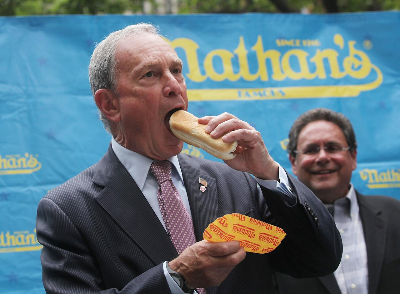 NEW YORK, NY - JULY 03: New York City Mayor Michael Bloomberg consumes a dog at the Nathan's Famous Fourth of July International Hot Dog Eating Contest weigh-in ceremony on July 3, 2013 in the Brooklyn borough of New York City. The annual hot dog eating event is expected to draw up to 40,000 fans on July 4, in the Coney Island section of Brooklyn. (Photo by Mario Tama/Getty Images)