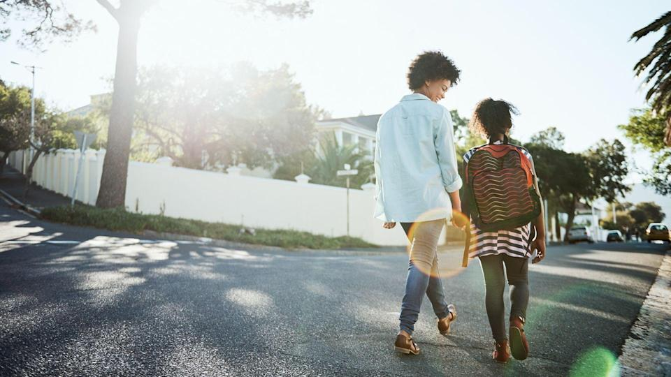 Rearview shot of a cheerful young mother and her daughter walking down the street together outside during the day.