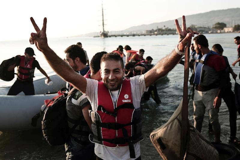 A migrant celebrates after arriving on the Greek island of Kos, on August 14, 2015 (AFP Photo/Angelos Tzortzinis)
