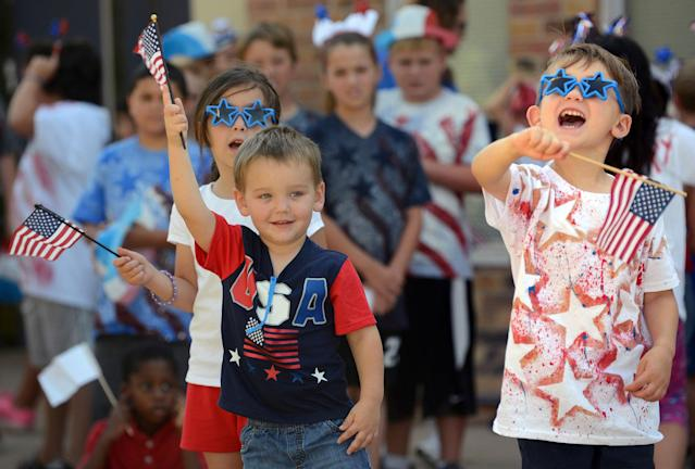 "<p>Carrie Baeza, left, Wyatt Cross, center, and Graysen Ziegler wave flags as they sing ""Wave Your Flag"" during an annual patriotic program Friday, June 30, 2017 during Summer Day Camp at Odessa Christian School in Odessa, Texas. A parade of decorated bicycles and tricycles followed the program. (Photo: Mark Sterkel/Odessa American via AP) </p>"