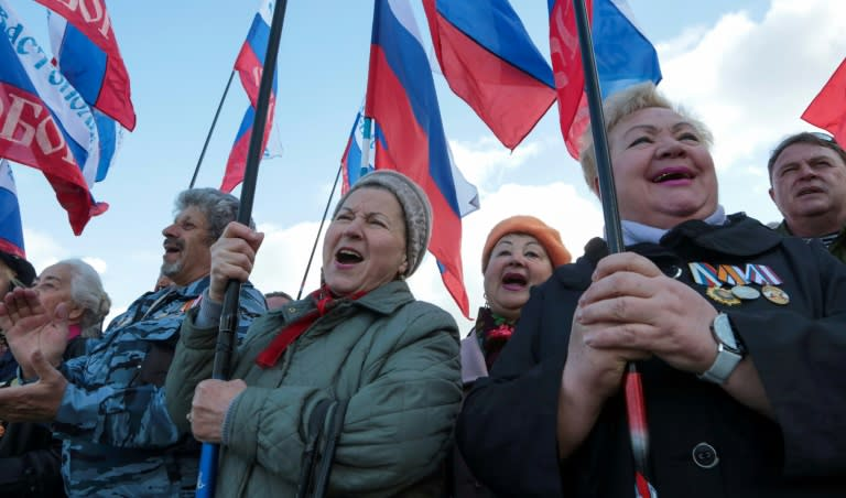 People wave the Russian national flag in Sevastopol on March 18, as they celebrate the third anniversary of the annexation of Crimea