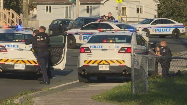 Police draw their weapons outside a multi-unit residence in the area of Cashin and Campbell avenues in St. John's' city centre Saturday, where an armed male was believed to be inside. The man was taken into custody Sunday morning. (Emma Grunwald/CBC - image credit)