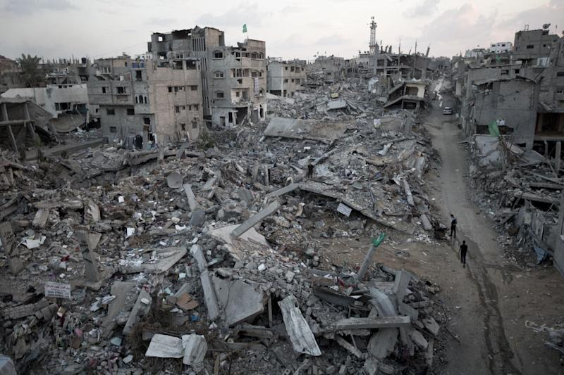 Palestinians walk through rubble of destroyed homes and buildings from the 50-day conflict between Hamas militants and Israel, in Gaza city on October 12 ,2014
