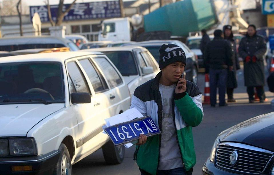 A man carries a licence plate at a used-car market in Beijing. To jump the queue for licence plates, people in the Chinese capital enter sham marriages. Photo: AFP