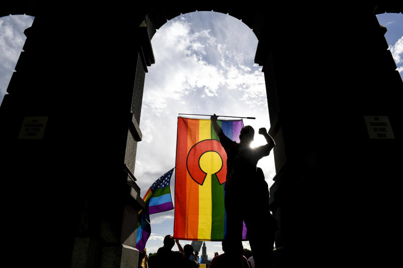 A protester holds a Colorado pride flag during a rally at the Colorado State Capitol after the Supreme Court ruled in favor of Jack Phillips, owner of Masterpiece Cakeshop. (AAron Ontiveroz via Getty Images)