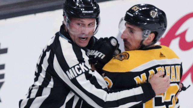 Brad Marchand is held back by an official. (AP Photo/Charles Krupa)