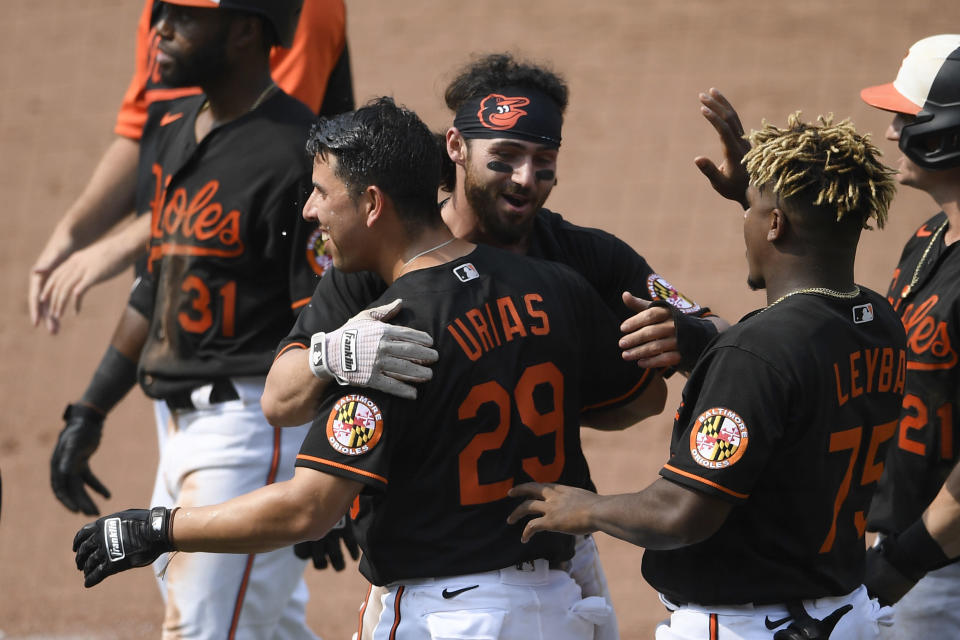 Baltimore Orioles' Ramon Urias (29) and Ryan McKenna, back, and Domingo Leyba (75) celebrate after a baseball game against the Washington Nationals, Sunday, July 25, 2021, in Baltimore. (AP Photo/Nick Wass)