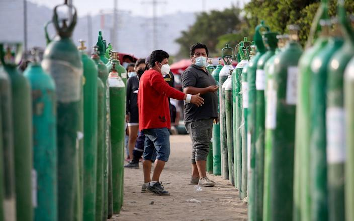 Buyers talk while waiting for their oxygen tanks to be filled in Lima, Peru - Raul Sifuentes/Getty Images South America
