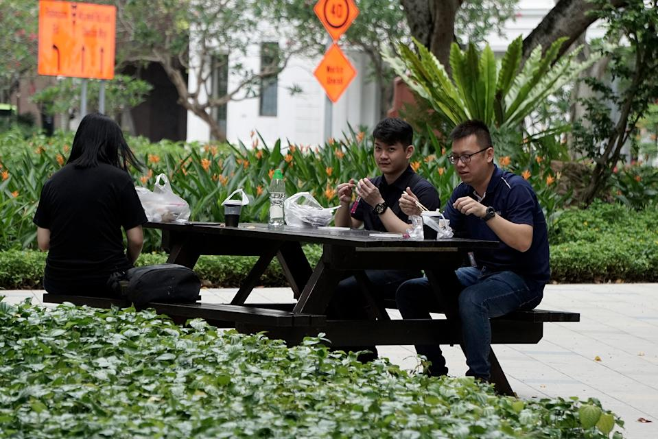 People seen eating at Telok Ayer Park on 7 April 2020, the first day of Singapore's month-long circuit breaker period. (PHOTO: Dhany Osman / Yahoo News Singapore)
