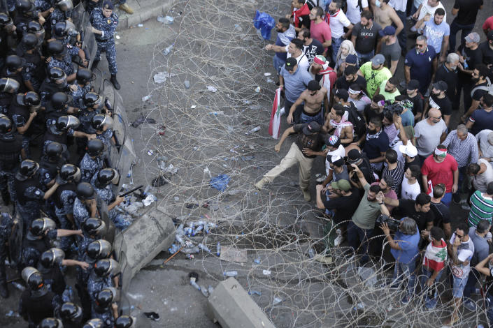 Riot police stand guard as anti-government protesters try to remove a barbed-wire barrier to advance towards the government buildings during a protest in Beirut, Lebanon, Saturday, Oct. 19, 2019. The blaze of protests was unleashed a day earlier when the government announced a slate of new proposed taxes, including a $6 monthly fee for using Whatsapp voice calls. The measures set a spark to long-smoldering anger against top leaders from the president and prime minister to the numerous factional figures many blame for decades of corruption and mismanagement. (AP Photo/Hassan Ammar)