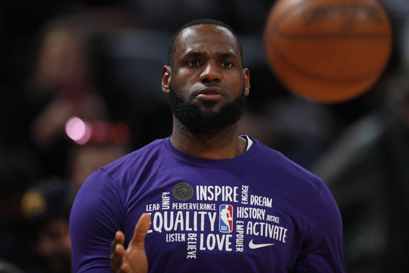 "LeBron James, in a purple shirt with sayings such as ""inspire, equality, love, activate"" prepares to catch a basketball."