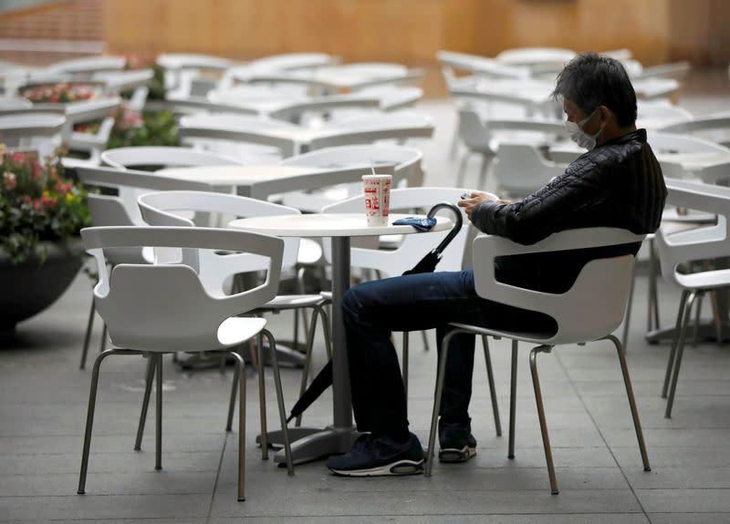 A man wearing a protective face mask, following an outbreak of the coronavirus disease, takes a rest next to empty seats at the Roppongi Hills complex in Tokyo