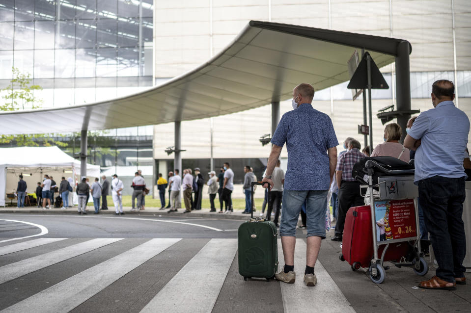 Travellers queue up at the test station for the coronavirus at Cologne/Bonn Airport in Cologne, Germany, Saturday, July 25, 2020. Free corona tests for returnees from countries designated as risk areas have begun at the German airports in Düsseldorf, Cologne / Bonn and Dortmund. (Marius Becker/dpa via AP)