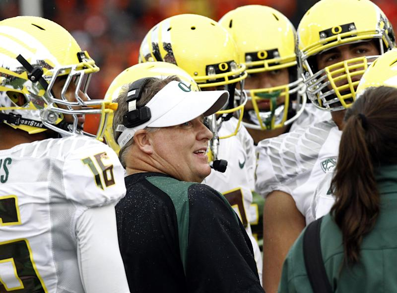 FILE - In this Nov. 24, 2012, file photo, Oregon coach Chip Kelly talks with his players during the first half of an NCAA college football game against Oregon State in Corvallis, Ore. The NCAA has taken away a scholarship and placed Oregon's football program on probation for three years for recruiting violations under previous coach Kelly.(AP Photo/Don Ryan)