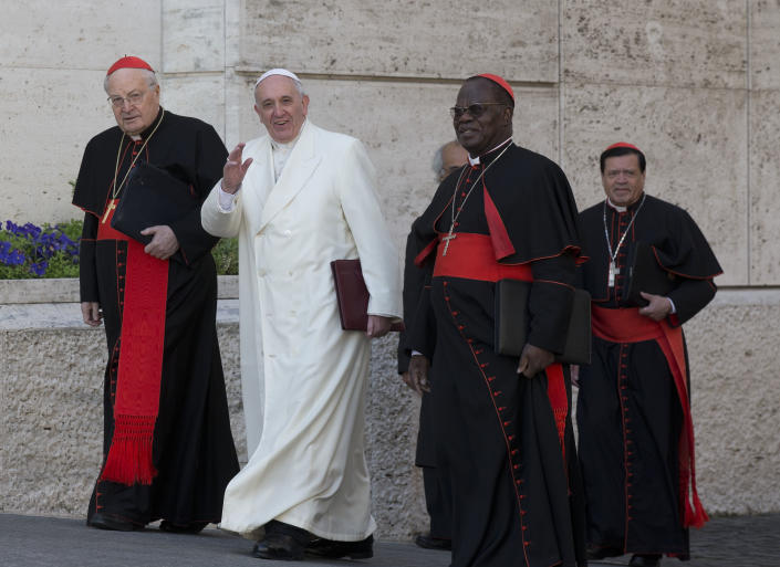 """Pope Francis, flanked by cardinals Angelo Sodano, left, Laurent Monsengwo Pasinya, second from right, and Norberto Rivera Carrera, arrives to open the morning session of an extraordinary consistory in the Synod hall at the Vatican City, Friday, Feb. 21, 2014. Pope Francis is leading a two-day meeting urging his cardinals to find """"intelligent, courageous"""" ways to help families under threat today without delving into case-by-case options to get around Catholic doctrine. He said the church must find ways to help families with pastoral care that is """"full of love.""""(AP Photo/Alessandra Tarantino)"""