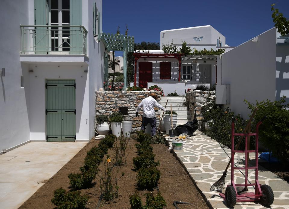 A man cleans the garden of a hotel in Agios Prokopios village, on the Aegean island of Naxos, Greece, Wednesday, May 12, 2021. (AP Photo/Thanassis Stavrakis)