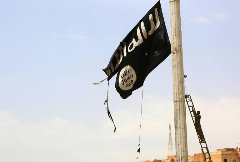 A member of the US-backed Syrian Democratic Forces removes an Islamic State group flag in the town of Tabqa on April 30, 2017