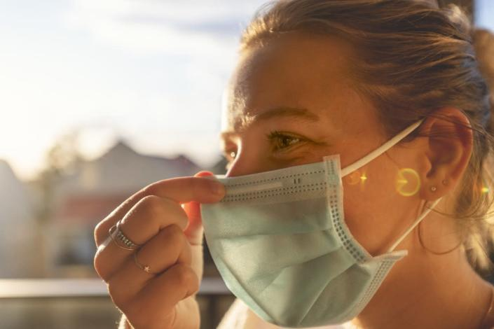 woman touching the nose of her surgical face mask while outside