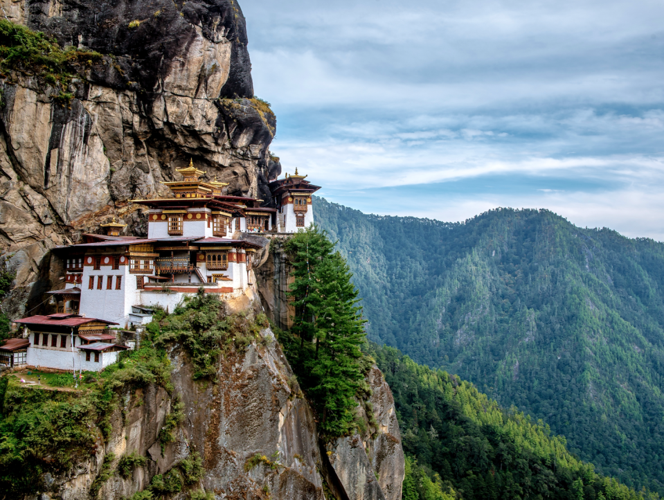 """<p>Majestically woven into the mountainside near Paro, Bhutan, sits Taktsang Palphug Monastery. Equally dramatic as it is stunning, this Buddhist temple complex–commonly known as the Tiger's Nest– is Bhutan's most prominent landmark. </p><p>Reaching the monastery requires a 4-5 hour round trip hike, but the views are well-worth the early wake-up call and 1,700 foot elevation gain. The entire path is carpeted with colorful prayer flags, vibrant prayer wheels, and unobstructed views of the monastery. There's no better time to visit than this upcoming October, when the long-awaited <a href=""""http://www.sixsenses.com/six-senses-bhutan-prepares-for-oct-2018-opening"""" rel=""""nofollow noopener"""" target=""""_blank"""" data-ylk=""""slk:Six Senses Paro"""" class=""""link rapid-noclick-resp"""">Six Senses Paro</a> property will open its doors just 20 minutes from the trail entrance. Consisting of five resorts spread over Bhutan's sweeping hills and valleys, the Paro property will ensure a spiritually enlightening stay and visit to Tiger's Nest, while overlooking the Paro Valley.<br></p>"""