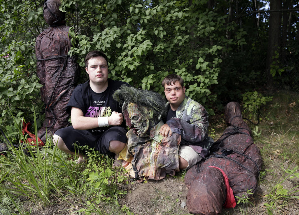 """FILE - In this July 12, 2016, file photo, Sam Suchmann, left, and Mattie Zufelt pose with ghoulish figures at Sam's home in Providence, R.I. The two young men who caused a sensation four years ago when they created their own gory zombie movie are back, this time in a documentary championed by a Hollywood luminary that chronicles their tenacious, years-long effort to see their silver screen dream come to fruition. """"Sam & Mattie Make a Zombie Movie,"""" was released Tuesday, April 6, 2021, on Apple TV. (AP Photo/Elise Amendola, File)"""