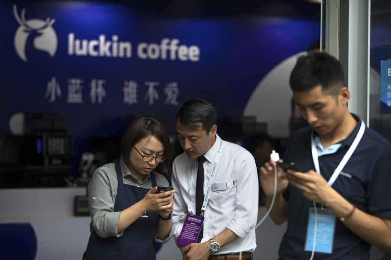 In this Aug. 15, 2018, photo, an employee helps a customer place an order on his smartphone at a Luckin Coffee pop-up shop at the World Robot Conference in Beijing. Shares of Luckin Coffee, a fast-growing rival to Starbucks in China, rose 20% in their U.S. stock market debut Friday, May 17, 2019. (AP Photo/Mark Schiefelbein)