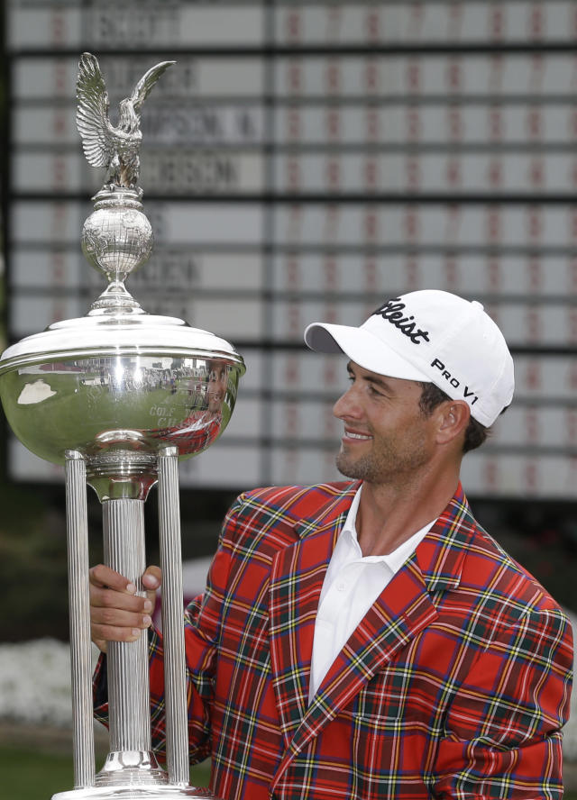 Adam Scott looks at the champion's trophy after winning the PGA Colonial golf tournament in Fort Worth, Texas, Sunday, May 25, 2014. (AP Photo/LM Otero)