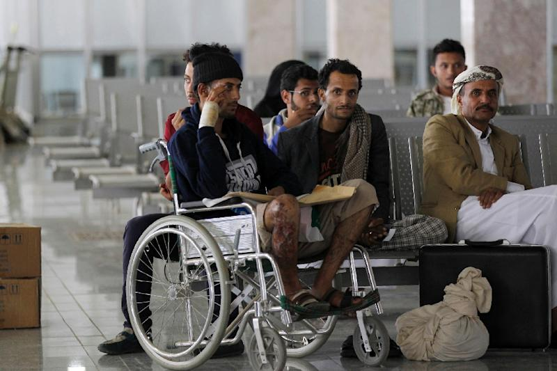 Wounded Yemeni men sit in the airport in Sanaa on October 15, 2016, as they wait for an Omani plane to evacuate them