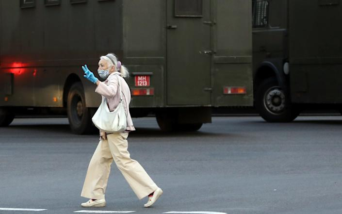 A woman flashes the V-sign near police vans in Minsk - TUT.BY/AFP via Getty Images