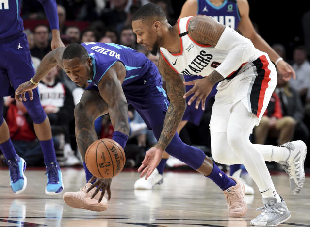 Charlotte Hornets guard Terry Rozier III, left, goes after a loose ball with Portland Trail Blazers guard Damian Lillard, right, during the first half of an NBA basketball game in Portland, Ore., Monday, Jan. 13, 2020. (AP Photo/Steve Dykes)