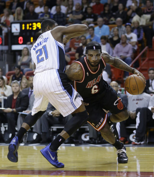 Miami Heat small forward LeBron James (6) drives around Orlando Magic small forward Maurice Harkless (21) during the first half of an NBA basketball game in Miami, Saturday, March 1, 2014. (AP Photo/Alan Diaz)