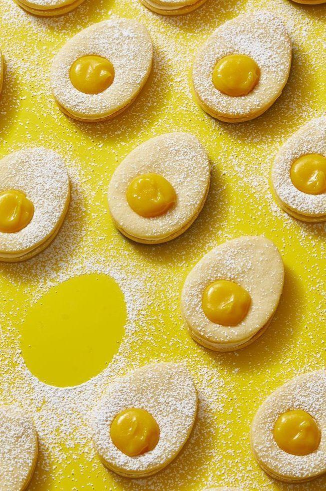 """<p>These adorable sandwich cookies are super fun to assemble with the kids, just don't let them get too carried away with sprinkling the powdered sugar. </p><p><strong><em><a href=""""https://www.womansday.com/food-recipes/a31980123/lemon-curd-egg-cookies-recipe/"""" rel=""""nofollow noopener"""" target=""""_blank"""" data-ylk=""""slk:Get the Lemon Curd Egg Cookies recipe."""" class=""""link rapid-noclick-resp"""">Get the Lemon Curd Egg Cookies recipe. </a></em></strong></p>"""