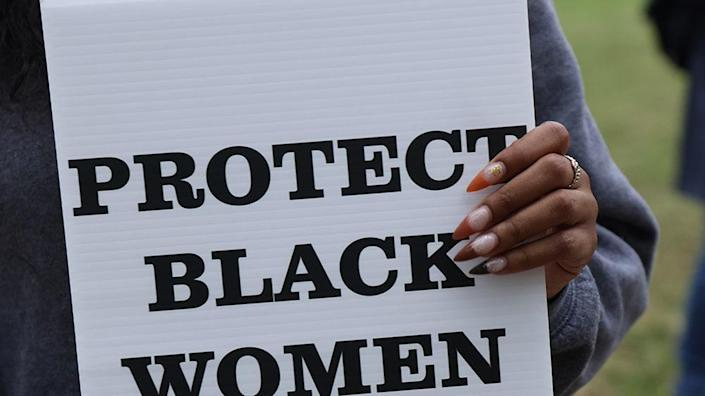 A woman holds a sign as she participates in a rally calling to protect black women October 2020 (Photo by Alex Wong/Getty Images)