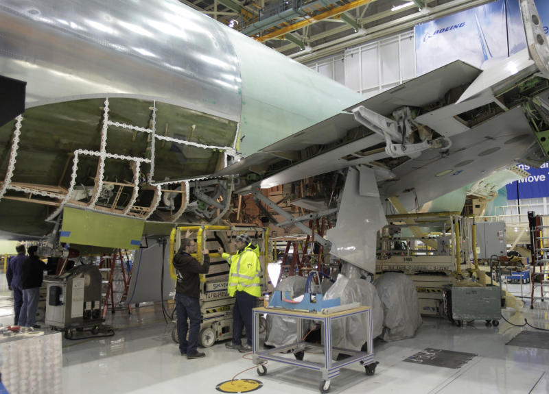 Boeing Co. workers stand next to a Boeing 767 being assembled in Everett, Wash. in this photo taken Friday, Feb. 25, 2011. The European plane-building company that lost out on a $35 billion refueling tanker deal isn't appealing the Air Force's decision to go with Chicago-based Boeing. The European Aeronautic Defence and Space Co. said Friday it won't ask the Pentagon to review the decision to have Boeing build nearly 200 giant airborne refueling tankers.  (AP Photo/Ted S. Warren)