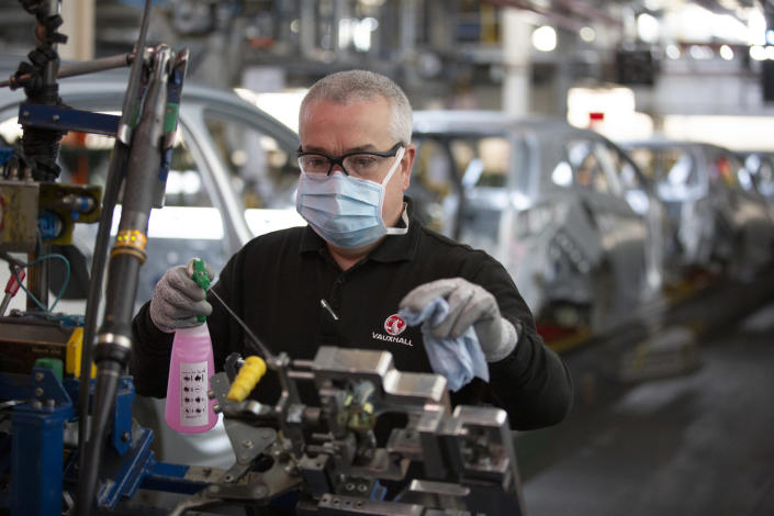 A member of staff at the Vauxhall car factory cleaning and disinfecting a workstation. Photo: Colin McPherson/Corbis via Getty Images