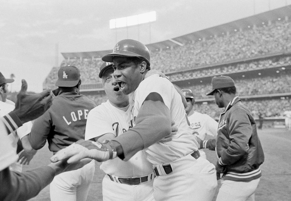 FILE - In this October 1977 file photo, Los Angeles Dodgers' Dusty Baker, right, gets a hug from manager Tom Lasorda after hitting a grand slam during the fourth inning against the Philadelphia Phillies in Game 2 of the NL Championship Series at Dodger Stadium in Los Angeles. Baker will get time in the spotlight back at Dodger Stadium next summer. The new Houston Astros manager will be invited to lead the American League in the All-Star Game at Dodger Stadium on July 14, Major League Baseball said Thursday, Jan. 30, 2020. (AP Photo, File)