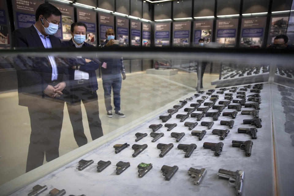 Chinese government officials look at a display of handguns seized in security operations in Xinjiang at the Exhibition of the Fight Against Terrorism and Extremism in Urumqi in northwestern China's Xinjiang Uyghur Autonomous Region, as seen during a government organized visit, on April 21, 2021. Four years after Beijing's brutal crackdown on largely Muslim minorities native to Xinjiang, Chinese authorities are dialing back the region's high-tech police state and stepping up tourism. But even as a sense of normality returns, fear remains, hidden but pervasive. (AP Photo/Mark Schiefelbein)