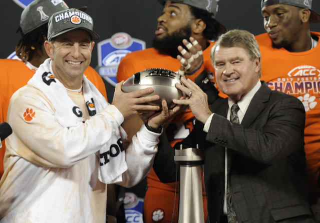 ACC commissioner John Swofford, left, gives Clemson head coach Dabo Swinney, left, the trophy after winning the Atlantic Coast Conference championship NCAA college football game against Miami in Charlotte, N.C., Saturday, Dec. 2, 2017. (AP Photo/Mike McCarn)