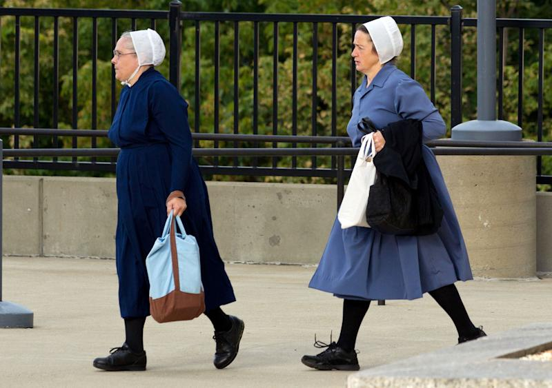 Two Amish women walk to the U.S. Federal Courthouse in Cleveland on Thursday, Sept. 20, 2012. The jury will begin their fifth day of deliberations in the trial of 16 Amish people accused of hate crimes in hair- and beard-cutting attacks against fellow Amish in Ohio. (AP Photo/Scott R. Galvin)