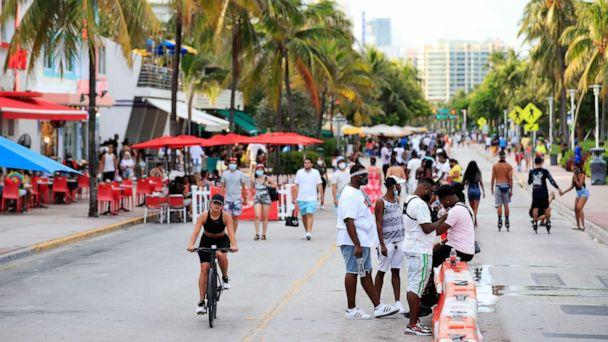 PHOTO: A woman rides her bike past pedestrians on Ocean Drive on July 3, 2020, in the South Beach neighborhood of Miami Beach, Fla. (Cliff Hawkins/Getty Images)