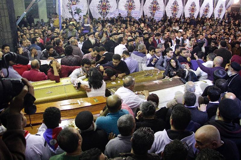 Egyptian Christians gather around and mourn by coffins during the late night funeral of the victims of a blast which killed worshippers attending Palm Sunday mass at the Mar Girgis Coptic Orthodox Church in the Nile Delta City of Tanta on April 9, 2017 (AFP Photo/STRINGER)