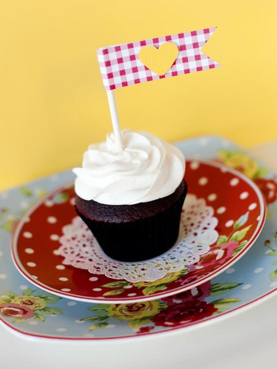 <p>Dress up simple cupcake with easy-to-make cupcake toppers. To create cupcake flags, cut a strip of patterned scrapbook paper one inch by 5-½ inches, and fold in half. Place a piece of double-sided tape the entire length of the backside. Place a four-inch lollipop stick in the crease, and fold over the paper. Trim the end to form a flag shape. Use a paper punch or hand cut a small heart; attach the heart to the flag with a foam dot to add dimension.</p>