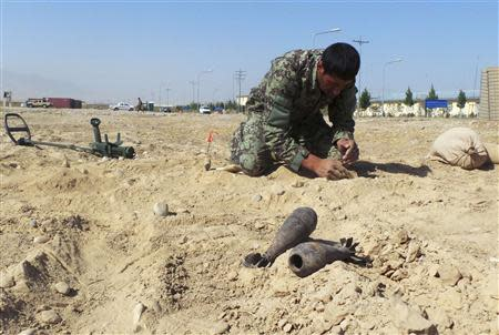 An Afghan army soldier from an improvised explosive devices (IED) school performs a demonstration in Mazar-e-Sharif in northern Afghanistan, October 5, 2013. REUTERS/Stringer