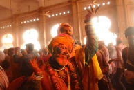 Hindu devotees dance as colored powder is thrown at them at Ladali, or Radha temple, at the legendary hometown of Radha, consort of Hindu God Krishna, during Lathmar Holi, in Barsana, India, 115 kilometers (71 miles) from New Delhi, on Tuesday, March 23, 2021. During the holiday, the women of Barsana beat men from Nandgaon, the hometown of Krishna, with wooden sticks in response to their teasing. (AP Photo)