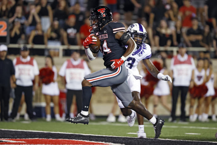 Texas Tech's Xavier White (14) scores a touchdown during the second half of the team's NCAA college football game against TCU, Saturday, Oct. 9, 2021, in Lubbock, Texas. (AP Photo/Brad Tollefson)