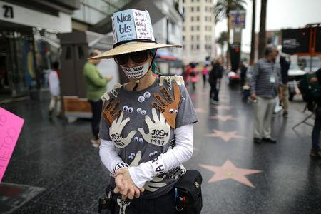 A woman who declined to give her name wears an outfit with the names of all the men in Hollywood who sexually harrassed her during a protest march for survivors of sexual assault and their supporters in Hollywood, Los Angeles, California U.S. November 12, 2017. REUTERS/Lucy Nicholson