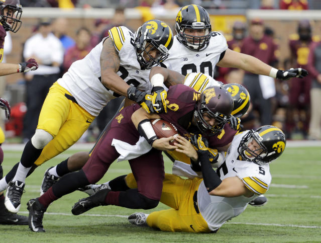 Minnesota quarterback Philip Nelson, center, is stopped by a group of Iowa defenders after a short gain in the second quarter of an NCAA college football game in Minneapolis Saturday, Sept. 28, 2013. Iowa beat Minnesota 23-7. (AP Photo/Ann Heisenfelt)