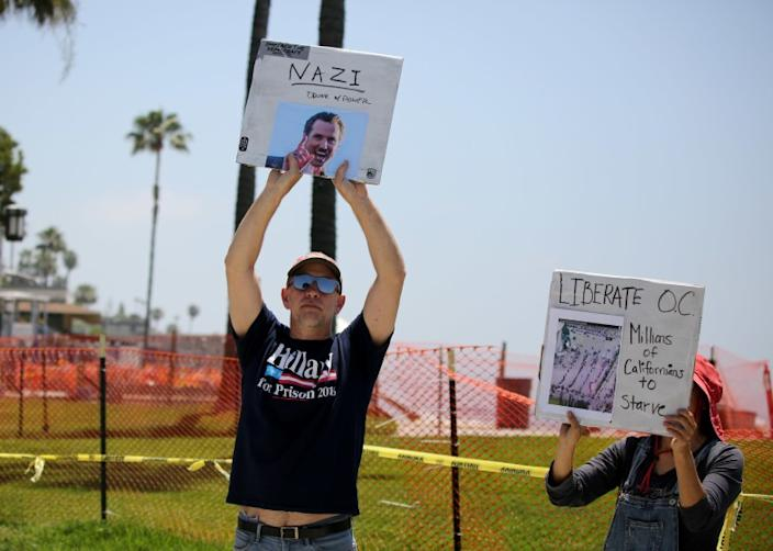 """A handful of protesters hold up signs next to the fenced-off Main Beach Park in Laguna Beach on May 2. <span class=""""copyright"""">(Los Angeles Times)</span>"""